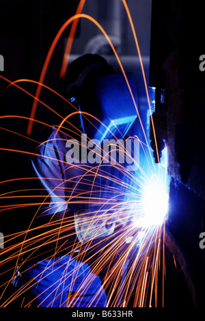 Welder working on a piece of metal with sparks flying - Stock Photo