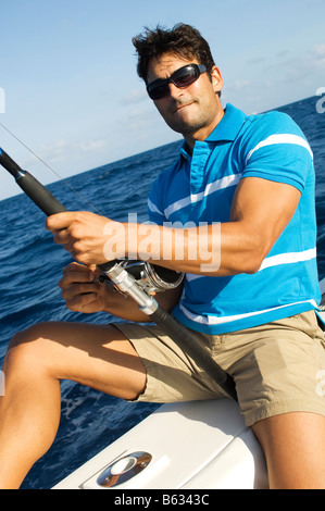 Mid adult man sitting in a boat and fishing - Stock Photo