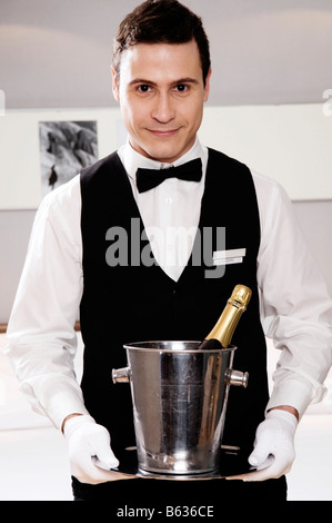 Portrait of a waiter holding a champagne bottle in an ice bucket - Stock Photo