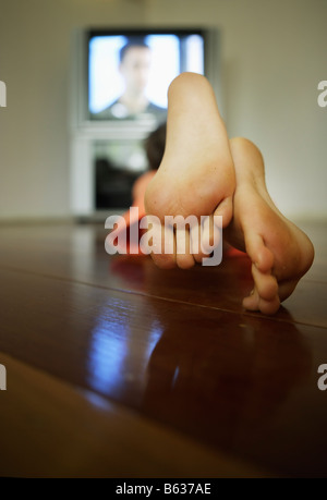 Six year old boy watches television - Stock Photo