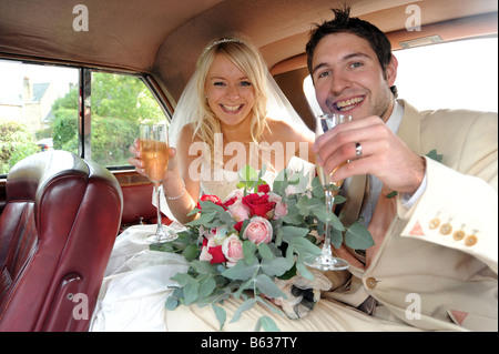 Newly wed couple inside their special car.
