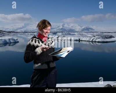 Icelandic girl with map at Jokulsarlon Glacial Lagoon, Breidamerkurjokull glacier, Eastern Iceland - Stock Photo