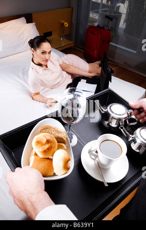 High angle view of a businesswoman lying on the bed and a waiter serving breakfast - Stock Photo