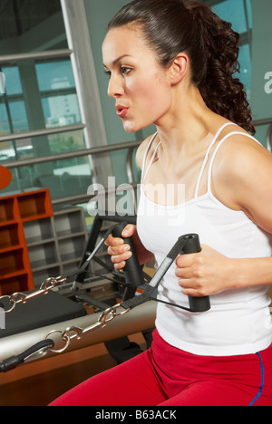 Side profile of a young woman exercising in the gym - Stock Photo