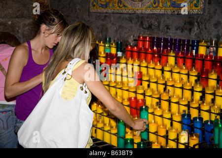 Worshippers lighting candles inside Montserrat Basilica, Montserrat, near Barcelona, Spain - Stock Photo
