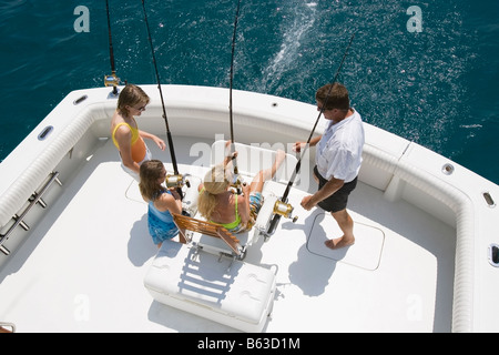 Mature couple with their children fishing in the sea - Stock Photo