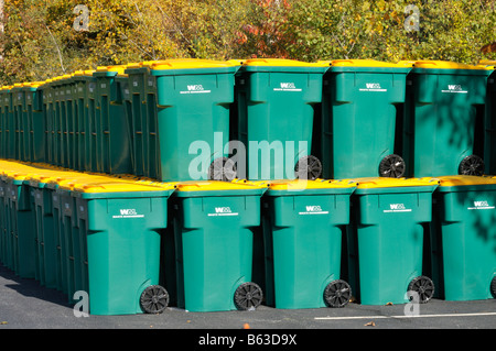 Large group of many new plastic recycling trash barrels or wheelie bins green with yellow lids stacked up in parking - Stock Photo