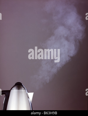 a color colour picture of a kettle boiling against a plain grey background - Stock Photo