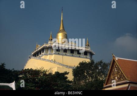 The Golden Mount or Mountain rises above Wat Saket, Bangkok, Thailand - Stock Photo