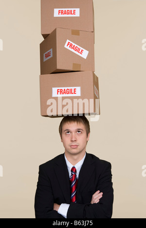 Young businessman balancing boxes on head - Stock Photo