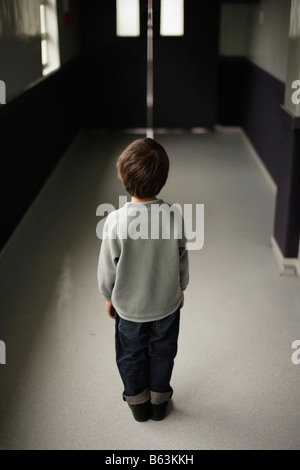 Six year old boy stands alone in school corridor - Stock Photo