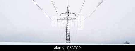 Electrical power lines on cloudy winter day cross snow covered field, Oberpfalz, Bavaria, Germany - Stock Photo