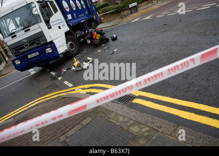 Police tape stretches across a south London junction  scene of collision between council recycling lorry and a motorbike - Stock Photo