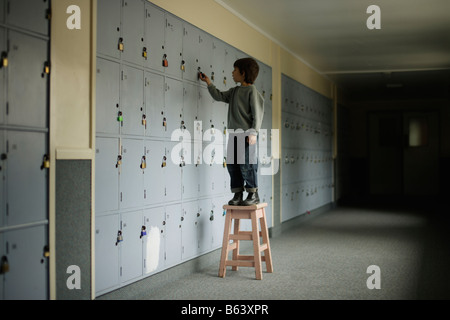 Six year old boy stands on stool in school corridor to reach top locker - Stock Photo