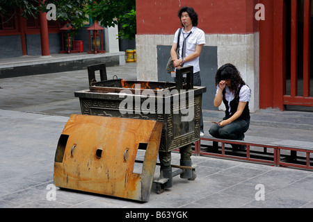 Chinese man and woman in religious offering, burning incense sticks in the YongHeGong lama temple in Beijing, China - Stock Photo