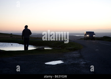 person walking on moors in winter. Dartmoor National Park sunset winter, Devon, England, UK - Stock Photo