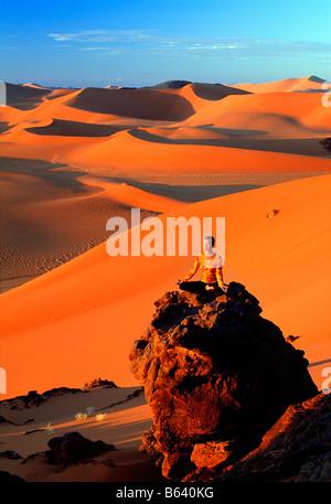 Algeria, near Djanet. Sand dunes and rocks. Woman meditating. Sahara Desert. - Stock Photo