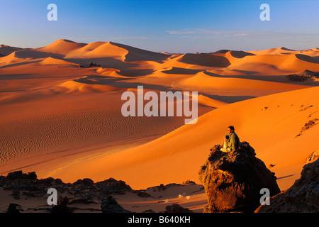 Algeria, near Djanet. Sand dunes and rocks. Tourist enjoying view. Sahara Desert. - Stock Photo
