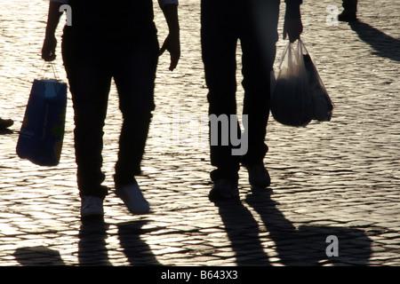 shadow people fast speed feet legs walking in sun in street in town - Stock Photo