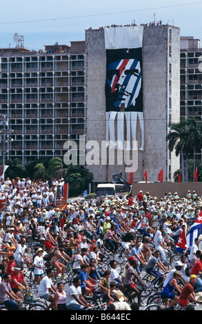 Supporters of government during May Day celebrations cycling past a portrait of Che Guevara, in Havana, Cuba, 1993 - Stock Photo