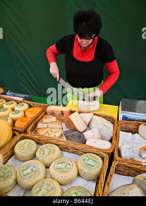 Woman on market stall cutting cheese Medemblik Netherlands - Stock Photo