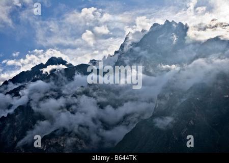 Morning clouds shroud Jade Dragon Snow Mountain, Tiger Leaping Gorge, Yunnan, China - Stock Photo