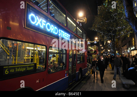 Oxford street Christmas decorations and bus with illuminated advertising panel and shoppers - Stock Photo