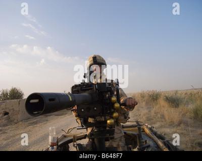 British Army soldier mans Grenade Machine Gun mounted on vehicle - Stock Photo