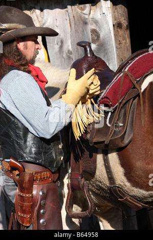 A cowboy taking off his leather gloves saddle fringe yellow - Stock Photo