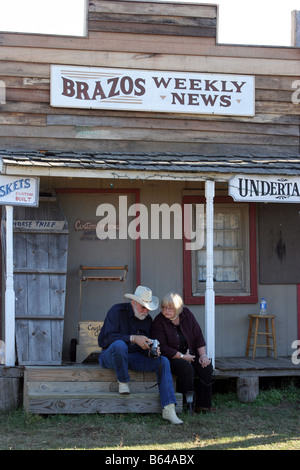 A couple enjoying viewing the photos on the back of a digital camera at an old west town set - Stock Photo