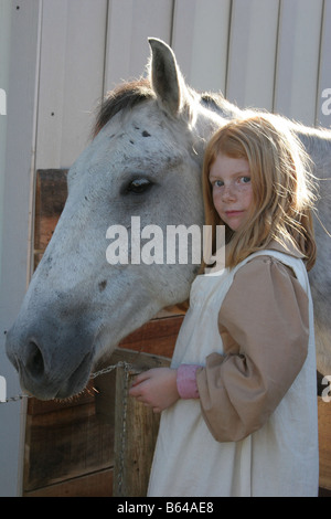 A young girl with a white horse - Stock Photo