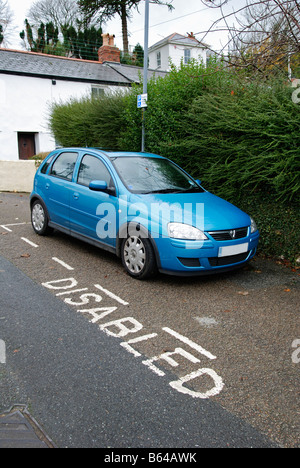 a blue car parked in a disabled parking bay - Stock Photo