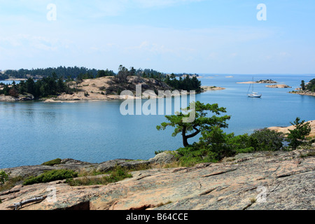 Little sailboat anchored in idyllic blue water of Georgian Bay Ontario Canada - Stock Photo