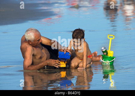 Brazil, Sao Paulo, Senior man and boy playing at Beach at Praia Enseada in Guaraja. - Stock Photo