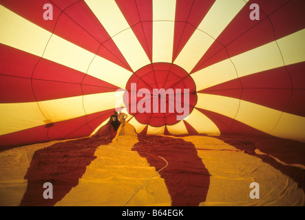 Colorful hot air balloon seen from inside as it is filled with hot air - Stock Photo