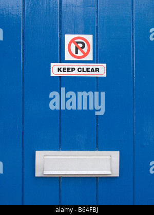 'No Parking' and 'Keep Clear' Sign on Blue Painted Door - Stock Photo