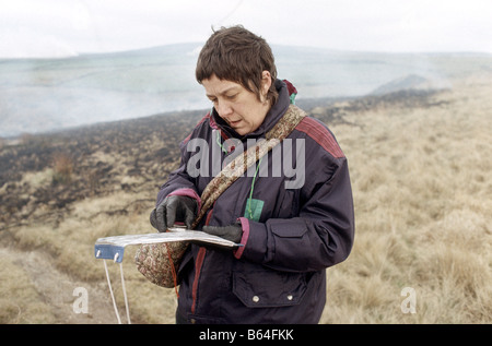 women looking at an ordinance survey map and using compass to find direction on a country walk - Stock Photo