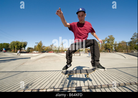 Young man doing a trick at a skate park - Stock Photo