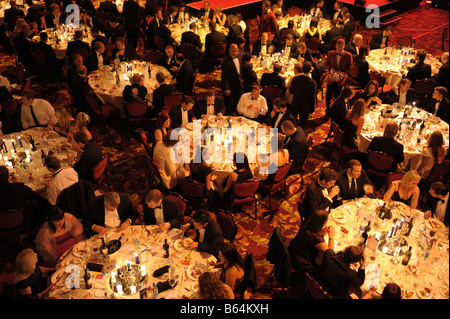 Large evening dinner function with many tables of people. Elevated aerial view. - Stock Photo