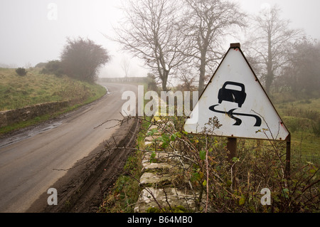 Old stone bridge with weathered 'Slippery Road' sign. - Stock Photo