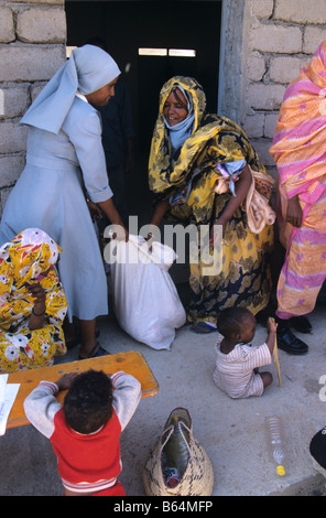 A Catholic nun working for a religious charity distributes food to poor villagers near Keren in the Eritrean highlands, - Stock Photo