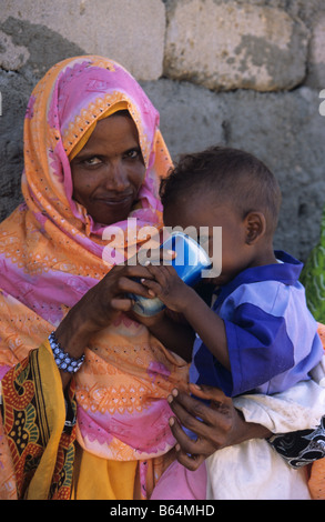 An Eritrean Muslim woman feeds her child at a food distribution centre, Keren, Eritrea - Stock Photo