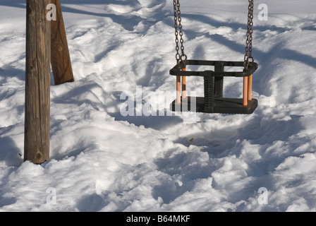 baby swing over snow covered ground - Stock Photo