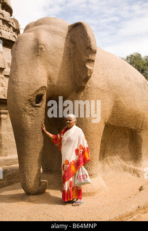 An Indian woman in a sari stands by one of the stone sculptures known as the Five Rathas in Mahabalipuram in India. - Stock Photo