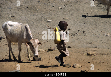 An Eritrean boy off to fetch water in the arid countryside near Keren, in the Eritrean Highlands, Eritrea - Stock Photo