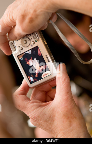 close up detail of the hands of an elderly person taking a photograph of young woman on her compact digital camera.UK - Stock Photo