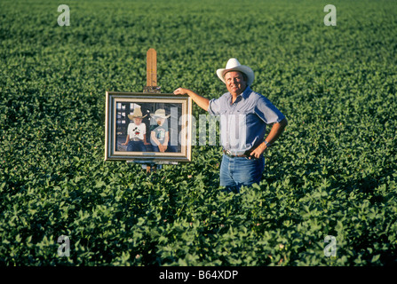 A portrait of Carl Clapp well known agricultural artist in his field of cotton with a painting of his two sons - Stock Photo