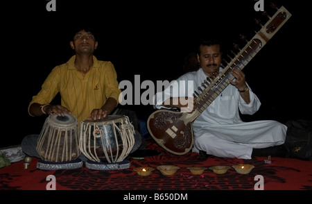 Two musicians playing the tabla drums and sitar in Varanasi India - Stock Photo