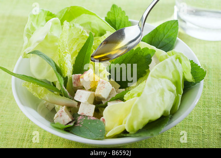 Spoon drizzling olive oil over salad of mixed greens and tofu cubes - Stock Photo