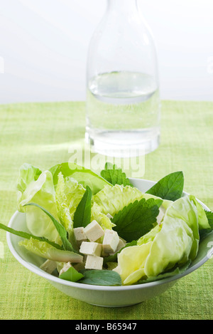 Salad of mixed greens and tofu cubes, carafe of water in background - Stock Photo